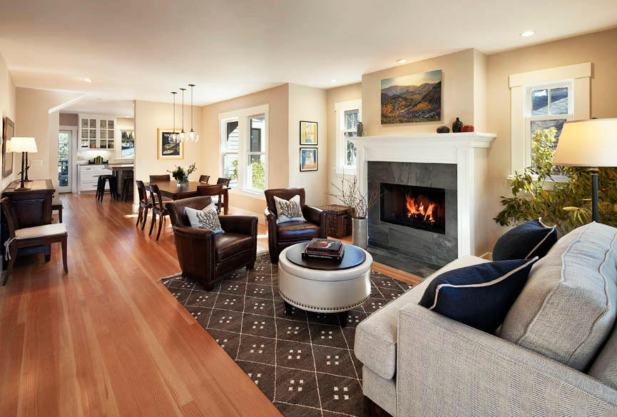Living and dining room with cherry wood floors, brown rug, fireplace and ottoman