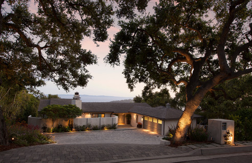 Evening exterior view of California ranch style house with oak trees