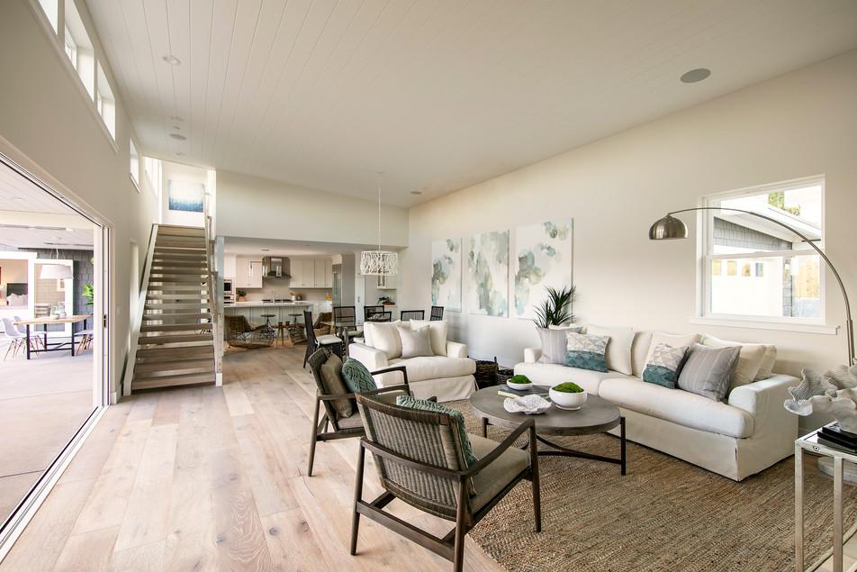 Modern coastal beach house living room with indoor/outdoor living. White walls, light oak floors, sisla rugs, rattan chairs