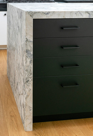 Black kitchen cabinets with marble top and waterfall side detail