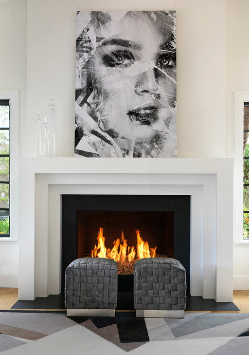 Modern living room fireplace white plaster white painted walls, graphic grey and black rug with grey ottomans. Oversize canvas artwork on mantle