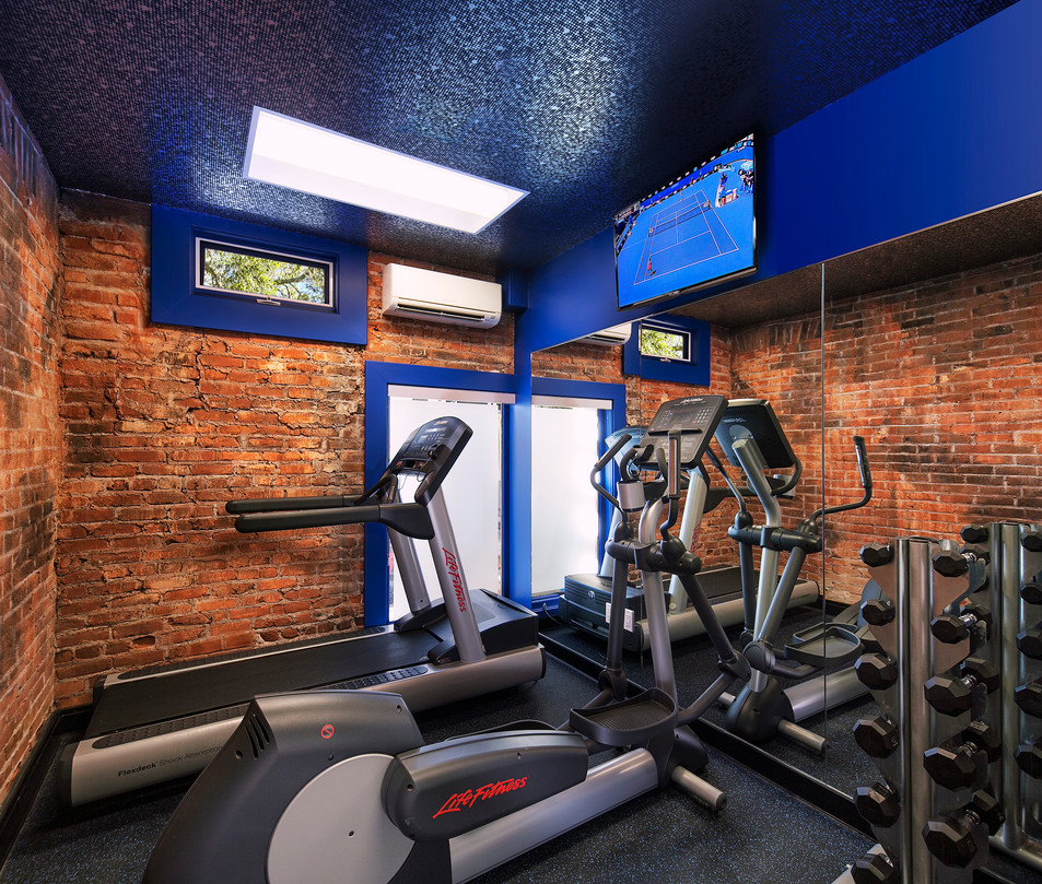 Hospitality interior design in Santa Barbara of hotel gym with brick walls and blue and silver wallpapered ceiling
