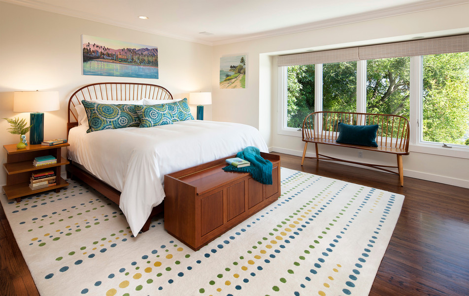 Master bedroom interior with bright rug and colorful custom pillows