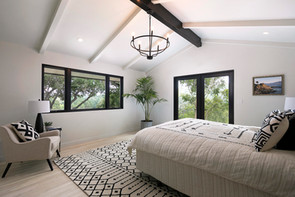 Master bedroom with white walls, vaulted, beamed ceiling and light oak wood floor. Contemporary black and white furniture