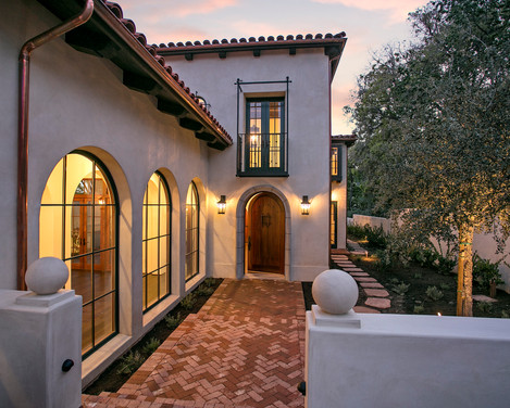 Spanish Mediterranean Elegance home exterior with brick pathway and arched windows