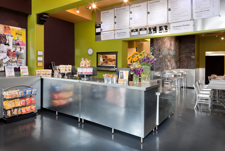 Colorful Deli interior design in Santa Barbara with green and purple walls, stainless steel counter and concrete floor