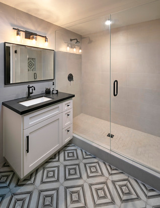 Bathroom with white vanity, diamond patterened floor tile and shower with light wall and floor tile
