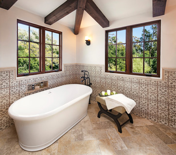 Spanish Mediterranean master bathroom with soaking tub, beamed ceiling, limestone tile floor, hand painted tile wainscotting