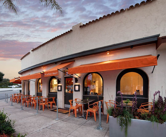 Corner Cafe with dark painted arched windows and orange accents