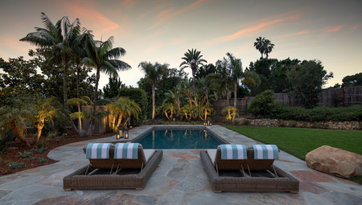 Elegant California Ranch Exterior backyard with flagstone patio, pool and chaises, landscape lighting and palm trees