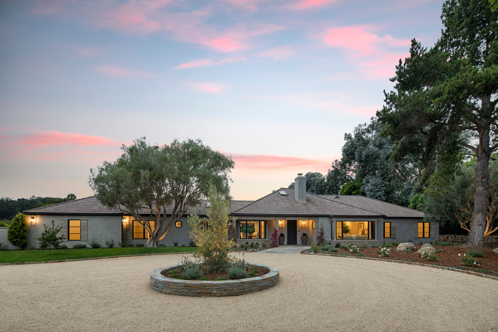 Elegant California Ranch front exterior of house with circular driveway, grey stucco black windows in Montecito