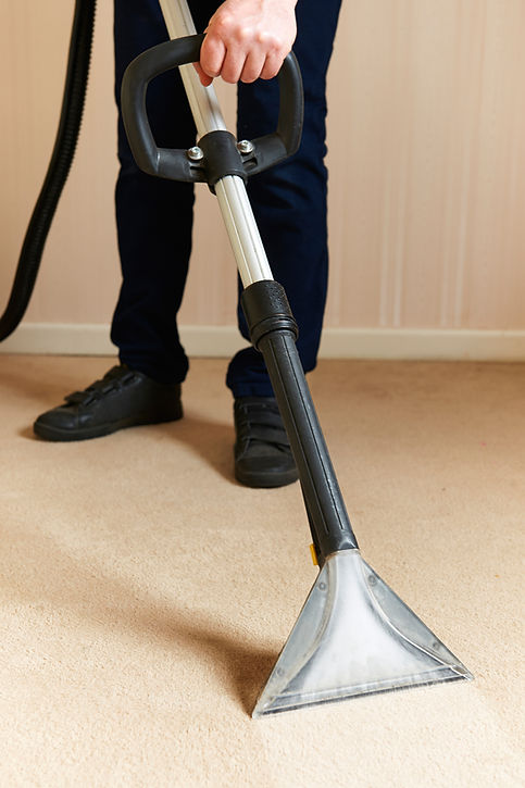 Man cleaning carpet with carpet wand