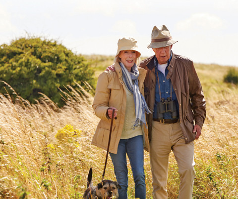 Older couple walking their dog outside.