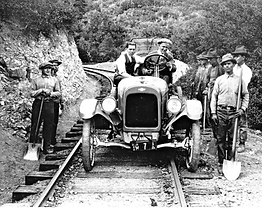 Old automobile and workers on Railroad Grade train tracks