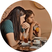 Two young women drinking soft drinks at a cafe