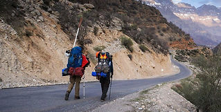 Two hikers walking along a mountain road.