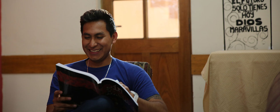 Young Bolivian man reading a book