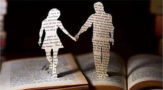 Hombre y mujere hecho de papel caminando sobre una Biblia
