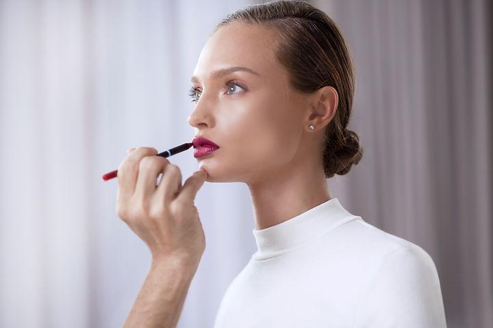 Makeup artist putting lip liner on