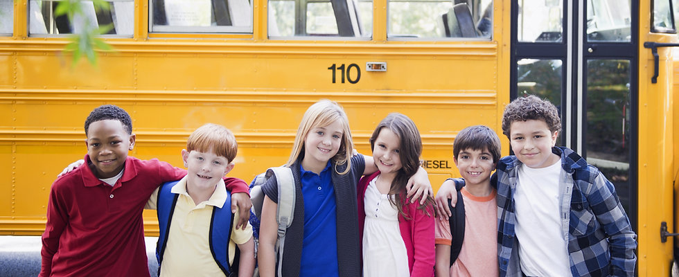 Group of Childern Standing in front of School Bus