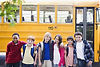 diverse group of school-age kids in front of yellow school bus