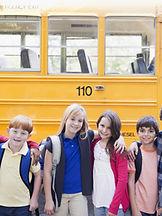 kids standing in front of a school bus ready for fieldtrip