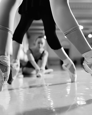 feet of young ballerinas in pointe shoes