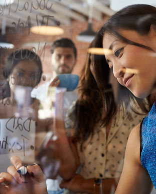 Businesswoman Writing Ideas On Glass Scr