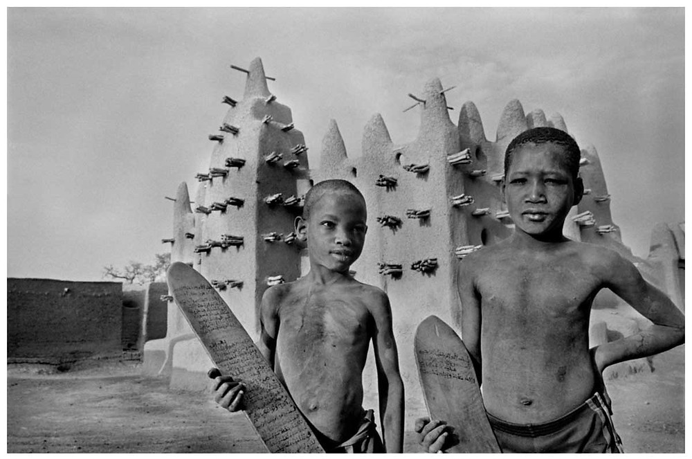 Allah O Akbar Pueblo de Severi Dos chicos están de pie frente a la mezquita. Van camino a la Medersa, la escuela coránica, donde aprenden a leer y escribir en las tablillas de madera que sostienen. Estas tablillas pueden ser borradas y reescritas en árabe, un idioma que los chicos descifran pero que no entienden. Malí 1988. © Abbas | Magnum PhotosLicense |
