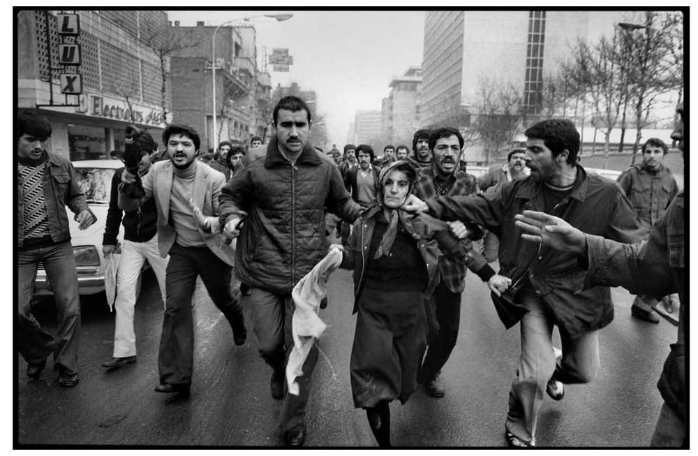 Abbas | Allah O Akbar Después de una manifestación en el Estadio Amjadiyeh en apoyo de la Constitución y de Shapour Bakhtiar, que fue nombrado Primer Ministro por el Shah antes de dejar el país, una mujer, que se cree que es partidaria del Shah es linchada por una turba revolucionaria. Teherán, Irán. 25 de enero de 1979. © Abbas | Magnum PhotosLicense |