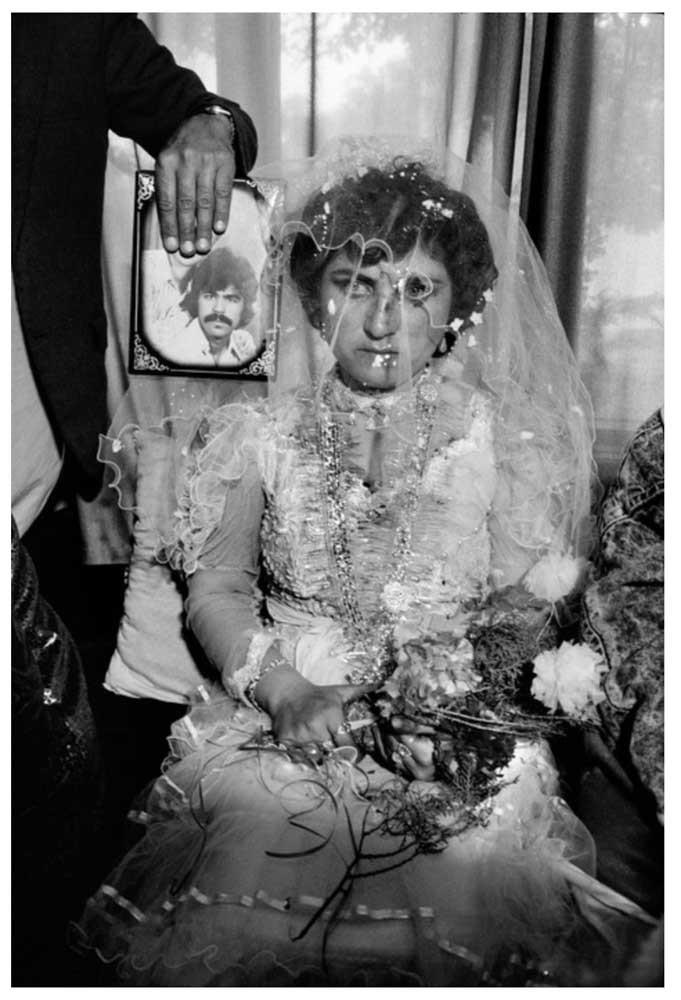 llah O Akbar Una boda por poderes: el prometido de la mujer, que emigró a Alemania, está presente sólo en la fotografía. Kabul, Afganistán. 1992. © Abbas | Magnum PhotosLicense |