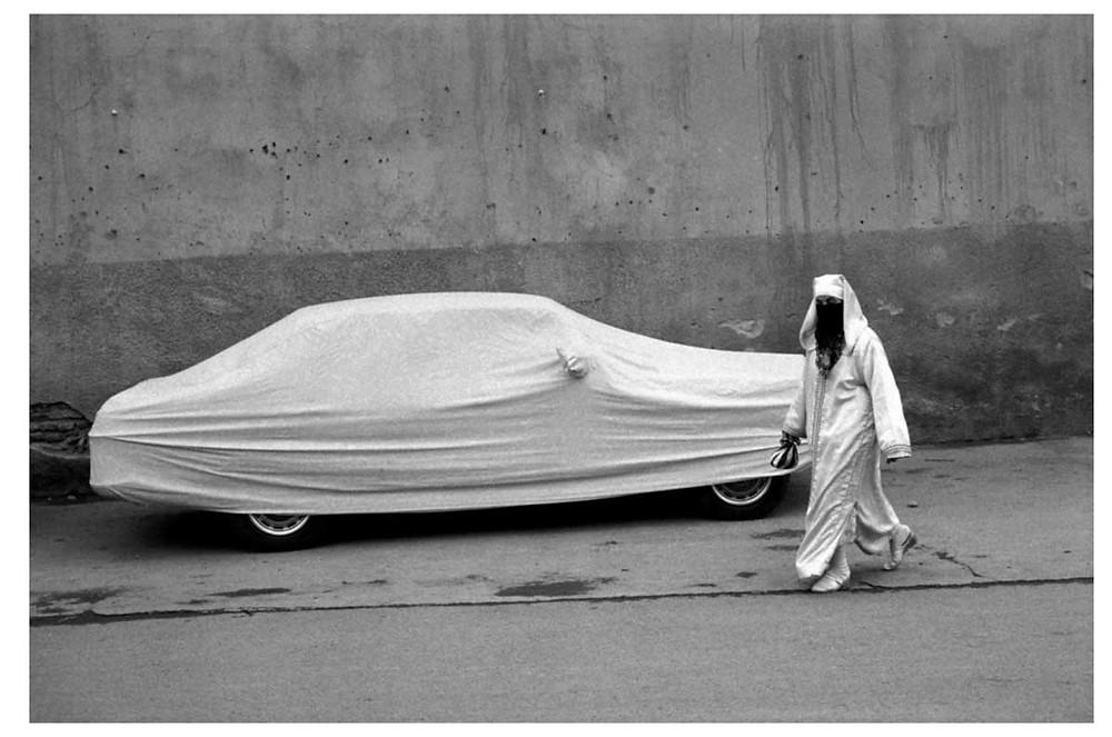 Allah O Akbar Una mujer y un coche. Ambos llevan el nigab, el velo que cubre tanto el cuerpo como la cara. Marrakech, Marruecos. 1991 © Abbas | Magnum PhotosLicense |