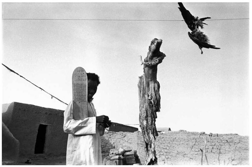 Allah O Akbar Un talibe (estudiante) sostiene una tablilla inscrita con suratos del Corán. El pájaro muerto que cuelga de la línea se utiliza para la brujería. El Islam negro cohabita con el animismo, y lleva muchos ritos paganos en sus rituales. Pueblo de Severi, Mali.1988. © Abbas | Magnum PhotosLicense |