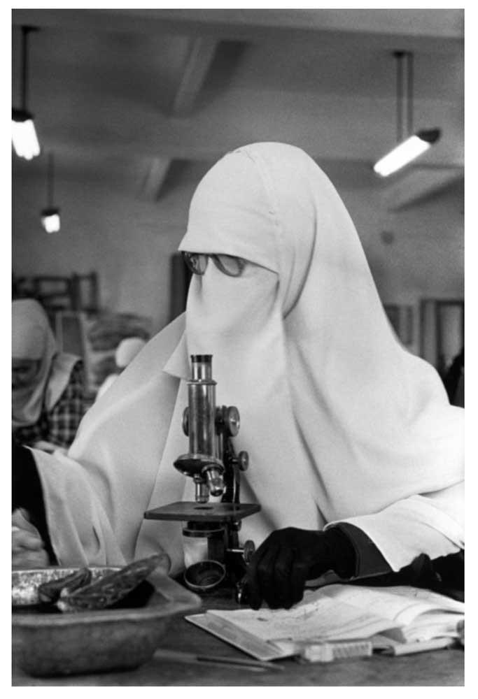 Allah O Akbar Un estudiante que lleva el nigab, el velo islámico completo frente a un microscopio en el departamento de biología de la Universidad de El Cairo. El Cairo, Egipto. 1987 © Abbas | Magnum PhotosLicense |