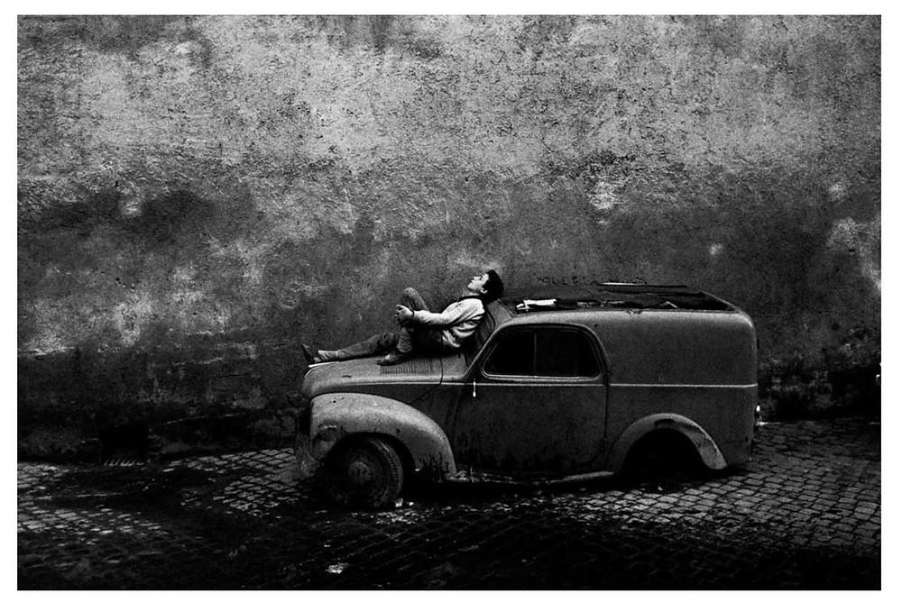 n niño se reclina sobre los restos de un coche en ruinas. Roma, Italia. 1962. © Bruno Barbey | Magnum PhotosLicense |