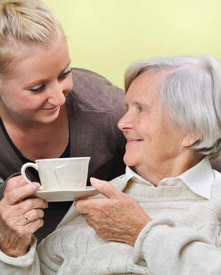 Senior woman with caregiver at home. MAN