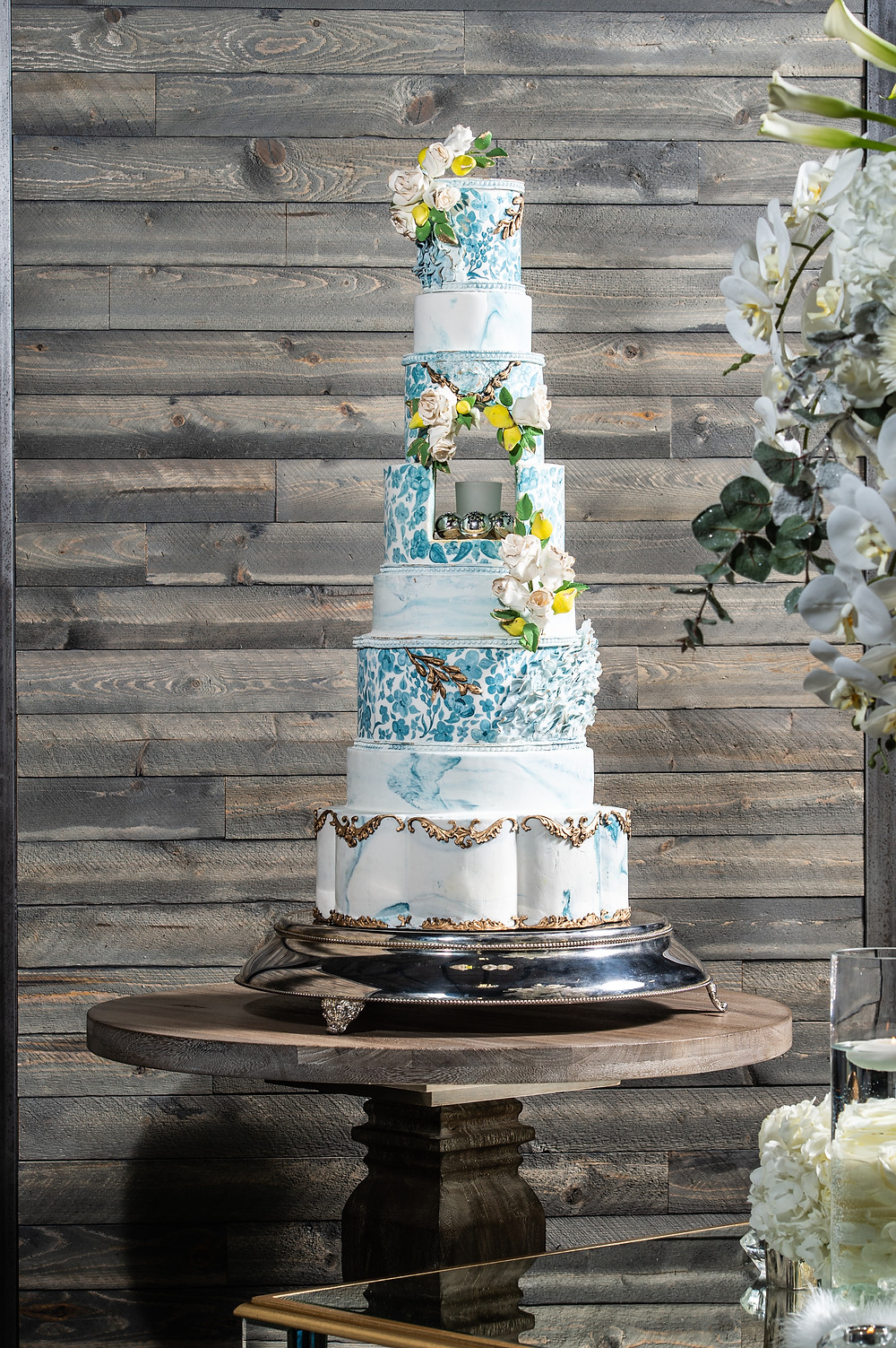 8-layer custom wedding cake with decorative flowers and hand-painted accents Bakers Cottage Cakes