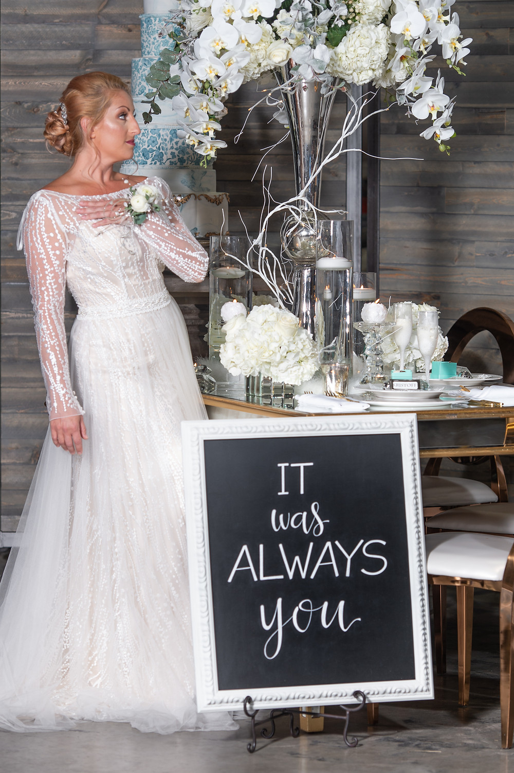 Model in white wedding dress with custom sign for displaying at wedding and floral arrangements