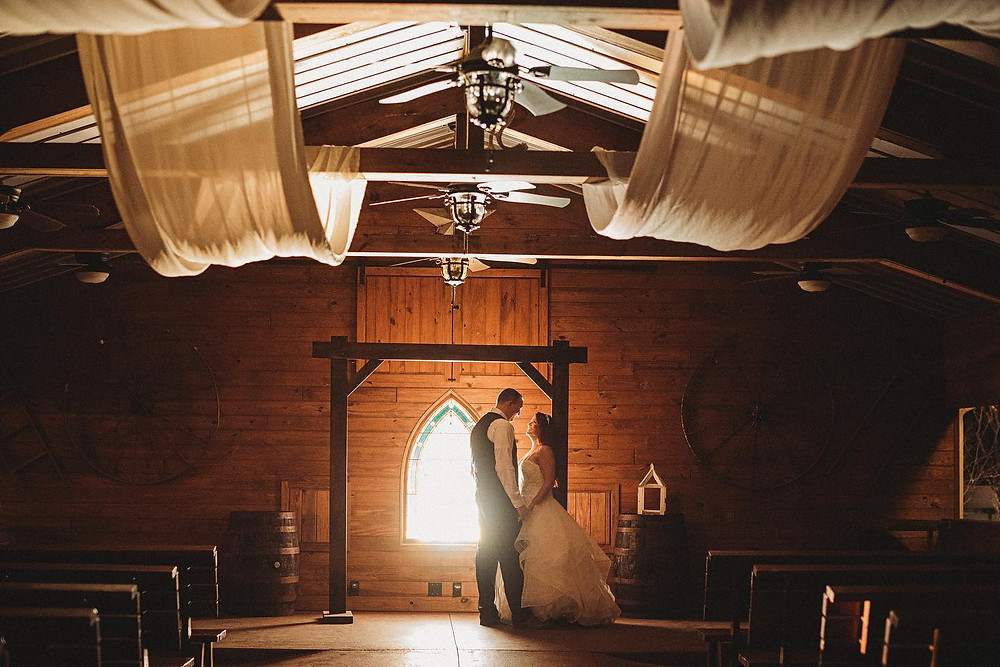 Bride and groom in barn with draping