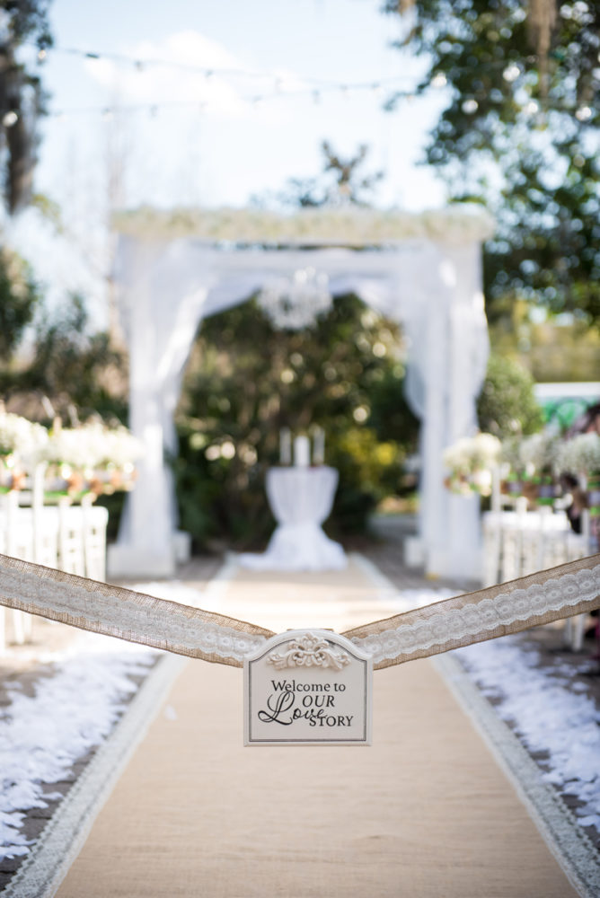 Wedding ceremony aisle with unity candles and draped arch