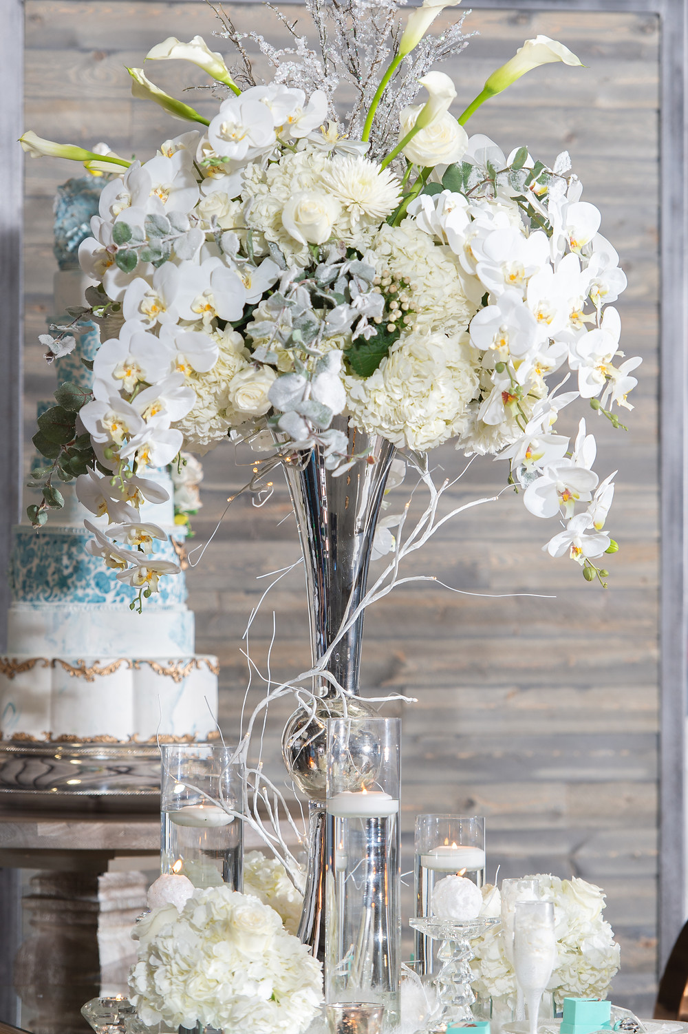 Large custom floral arrangement for wedding with smaller arrangements on table