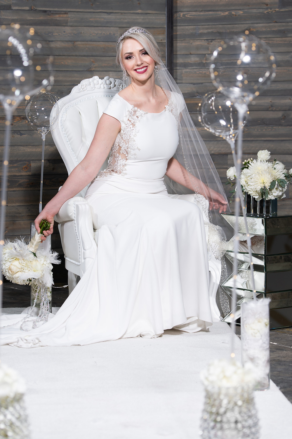Model in white wedding dress with custom bubble lighting and white floral arrangements