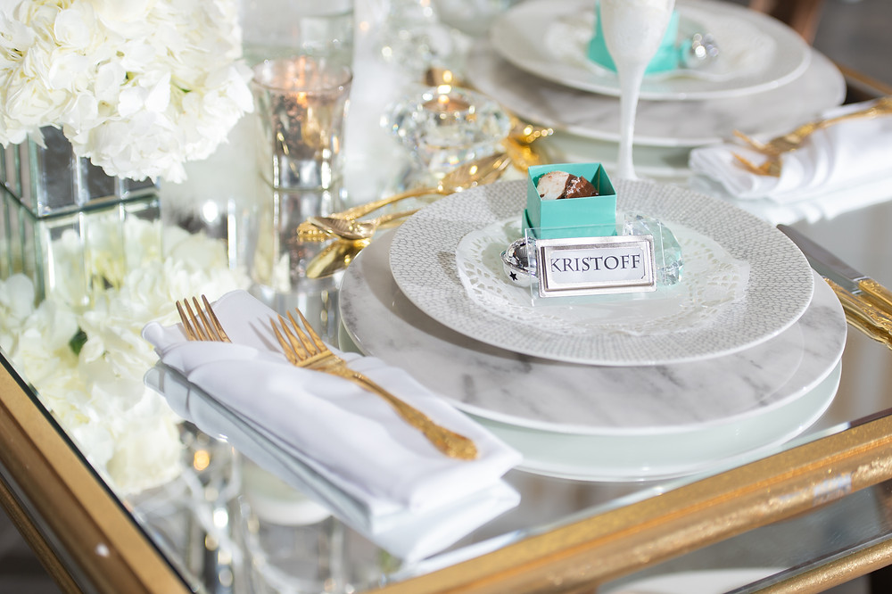 Frozen-inspired table setting with mirrored table, gold flatware and marble charger and plate