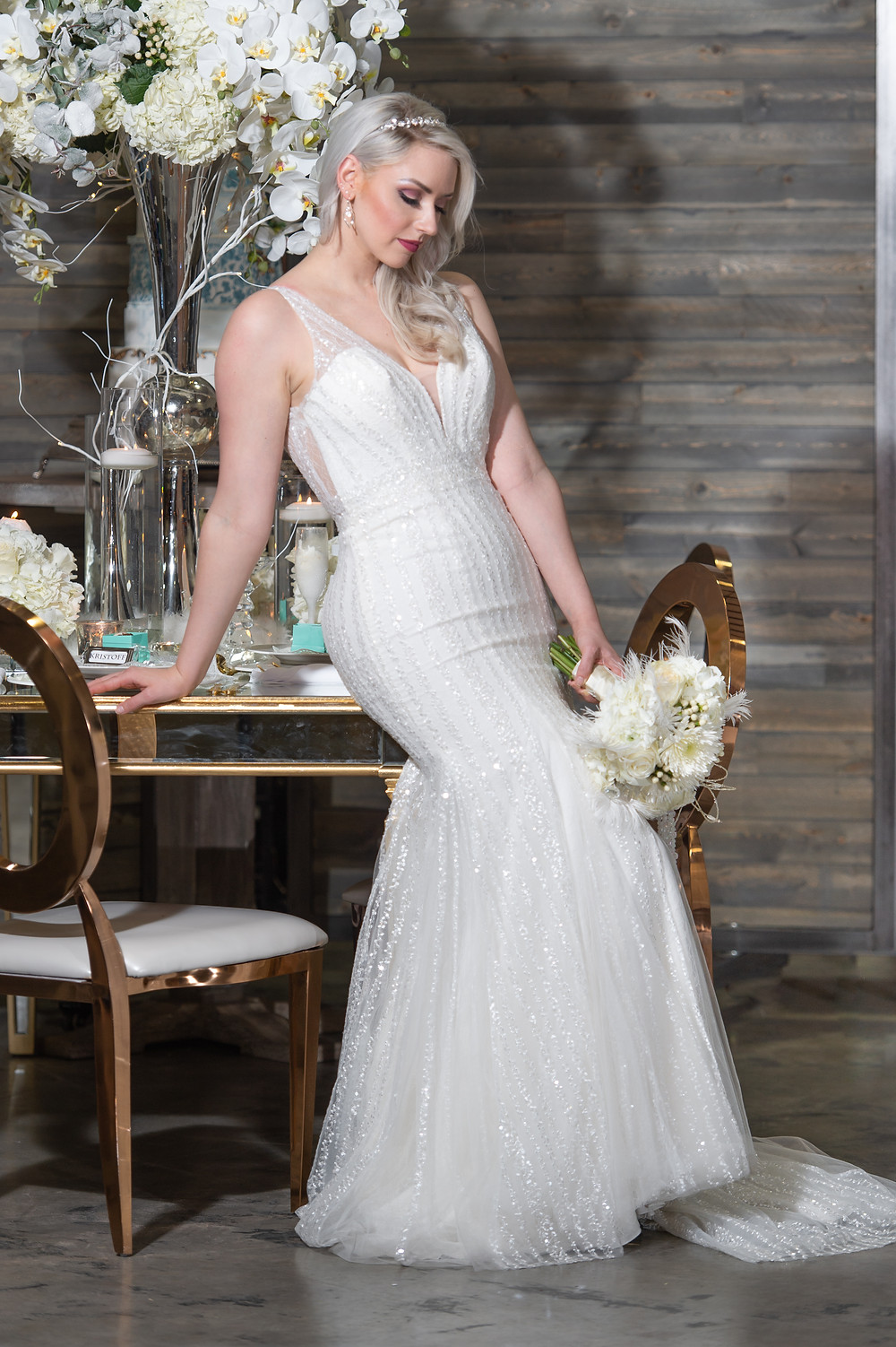 Model in white mermaid-style wedding dress and custom decorative headpiece with bouquet