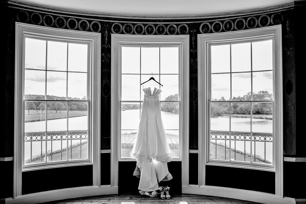 wedding dress hanging in bay window black and white