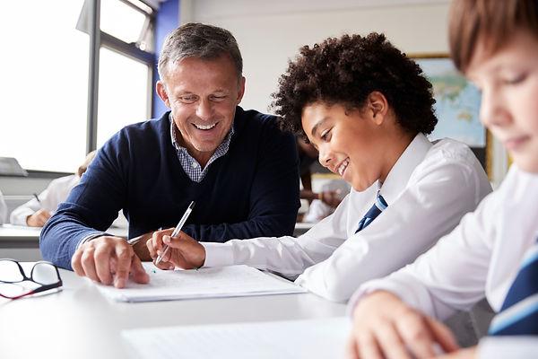 high-school-tutor-giving-male-student-we