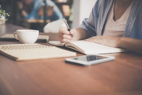 woman-writing-on-a-notebook-beside-teacu