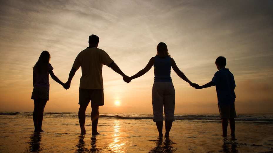 Family Holding Hands on Beach Watching t