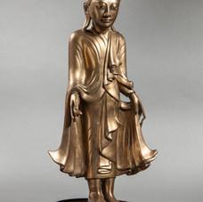 Lot.25 BUDDHA DEBOUT en posture hiératique déployant les pans de sa robe monastique utarasanga aux plissées bouillonnants, tenant dans sa main droite le fruit de cédrat. Son visage serein est surmonté de la protubérance crânienne ushnisha symbole de sa connaissance. Bronze nettoyé de sa patine, laqué ocre à la coiffe et incrusté de sulfure aux yeux. Birmanie. Royaume de Mandalay. 19 ème siècle.  48cm. Est 1.500/2.000 €