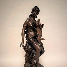 Lot.26 MATHURIN MOREAU (1822-1912) Jeune femme au cupidon  Bronze à patine brune médaille. Signé sur la terrasse « Mat. Moreau».Base en marbre. Fonte ancienne. Haut. 55 cm (sans le socle) – 57 cm avec le socle Est. 1.500/2.000 €